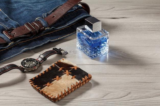 男性の香水、革のストラップ、灰色の木製の背景に革のベルトと革の財布とブルージーンズで時計