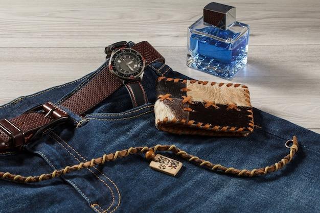 男性の香水、革のストラップ付きの時計、革のベルト付きのブルージーンズ、灰色の木製の背景に革の財布とお守り