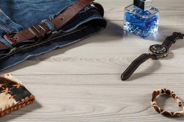 男性の香水、革のストラップ、灰色の木製の背景に革のベルト、お守り、革の財布とジーンズ