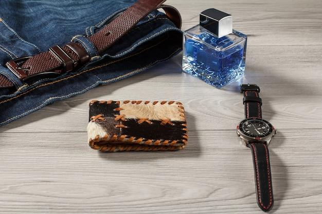 男性の香水、革のストラップ、灰色の木製の背景に革のベルトと革の財布とジーンズ