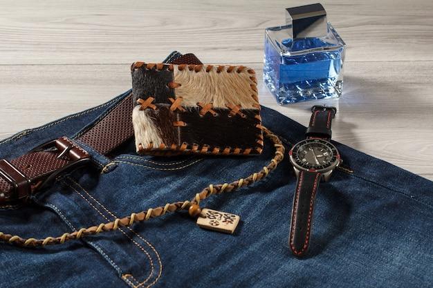 男性の香水、革のストラップ付きの時計、革のベルト付きジーンズ、灰色の木製の背景に革の財布とお守り