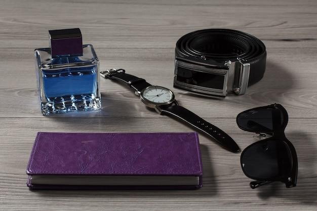 男の香水、革ストラップ付き時計、金属バックル付き革ベルト、紫色のカバーのノートブック、灰色の木製の背景に黒いサングラス