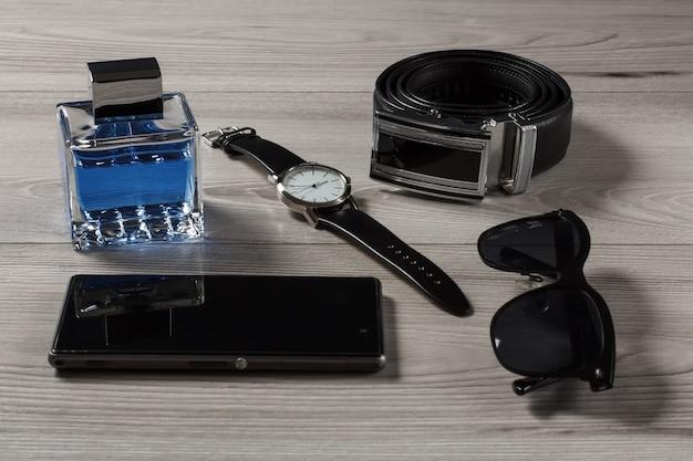 男性の香水、革のストラップ付きの時計、金属製のバックル付きの革のベルト、電話の販売、灰色の木製の背景に黒いサングラス