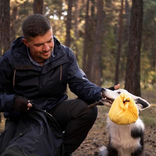 Мужчина гладит красивую черно-белую собаку