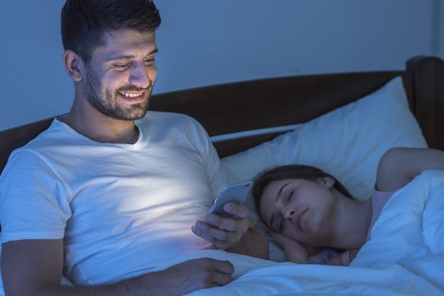 The man phone near the sleeping woman. night time