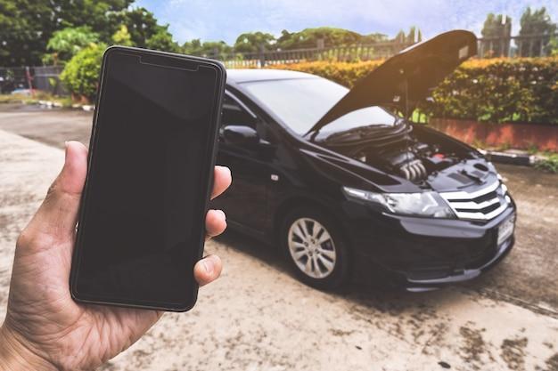 壊れた車で助けを求めて電話をかける男