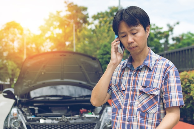 Man phoning for help with a broken down car