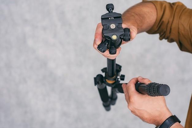 남자 사진가는 사진과 비디오를 촬영하기 위해 손에 전문 삼각대를 들고 있습니다.