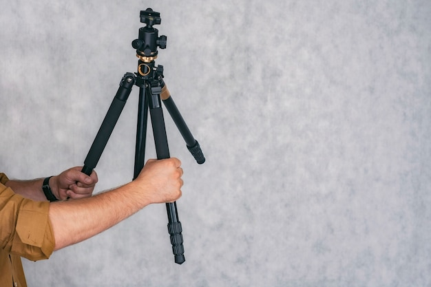 Man photographer holds a professional tripod in his hands for shooting photos and videos.