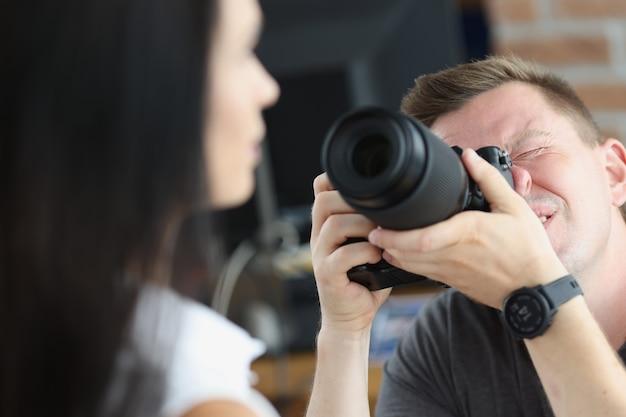 남자 사진작가가 여성 인물 사진 훈련 개념의 사진을 찍고 있다