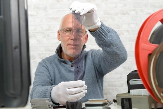 Man photographer looking at negative film