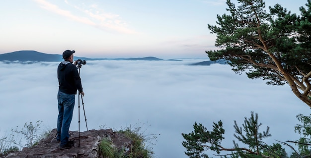 A man photographer in the mountains takes pictures with a camera on a tripod of nature and the morni...