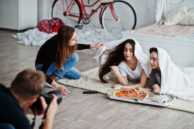 Man photographer shoot on studio twins girls who are eating pizza. assistant helps in shooting. professional photographer on work.