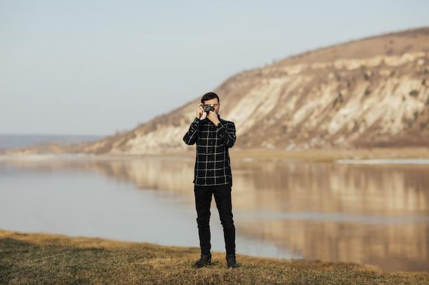 山の中でビンテージカメラで写真を撮る男の写真家