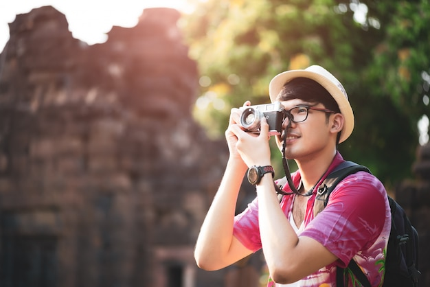 Man photographer traveler with backpack taking photo with his camera
