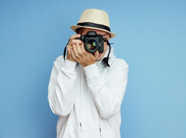 그의 손에 slr 카메라를 가진 남자 사진 작가가 사진을 찍습니다
