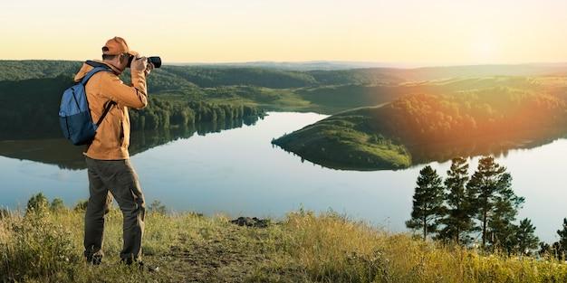 배낭과 카메라를 들고 일몰 산의 사진을 찍는 남자 사진사. 활동적인 건강한 라이프 스타일 모험 여행 휴가. 배너.