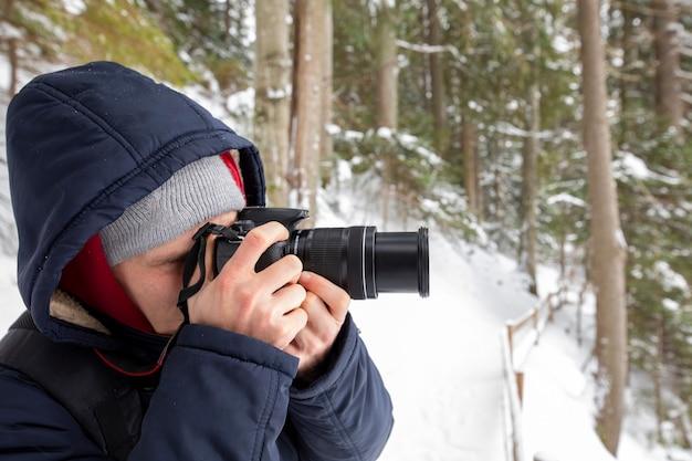 カメラを持つ男の写真家は、冬の森の風景の写真を撮ります。