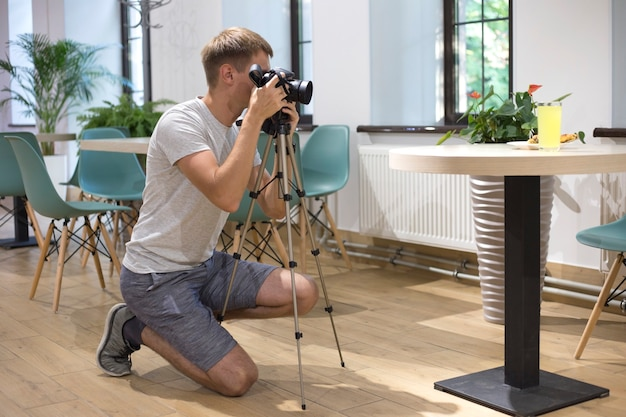 Man photographer with tripod and digital slr camera takes pictures of food in cafe food photography