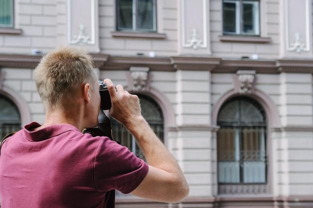ヴィンテージカメラで古い家を撮影する男