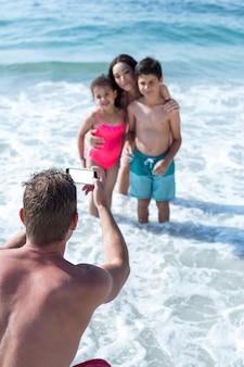 얕은 물에서 어린이와 아내를 촬영하는 사람