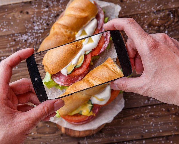 Man photographing sandwich with sausage