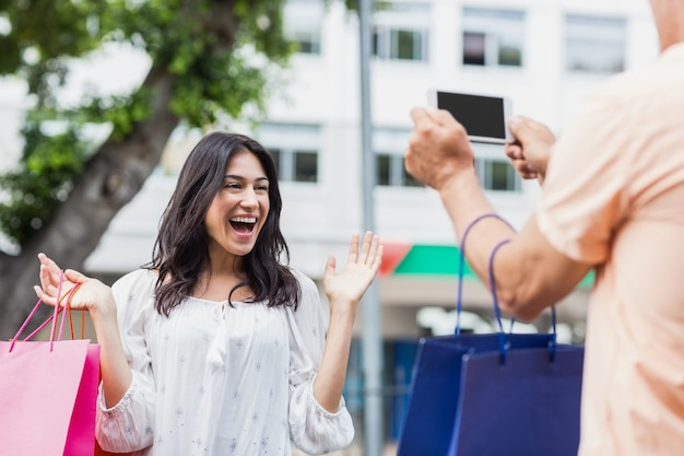Man photographing smiling woman with shopping bag