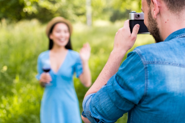Man photographing waving woman in countryside