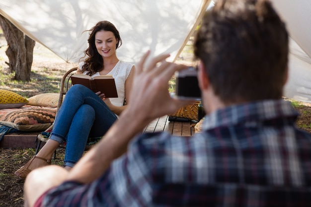 Man photographing woman reading book