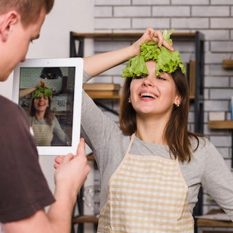 Man photographing woman with salad leaf on head