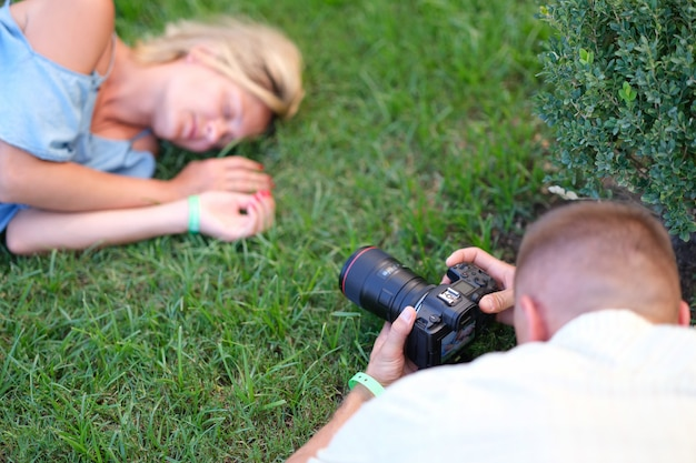 Man photographing young woman sleeping on grass