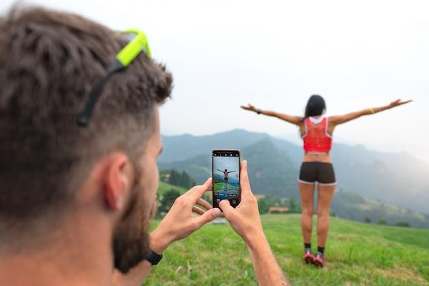 남자는 산악 여행 동안 자신의 스마트 폰으로 스포티 한 여자 사진