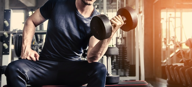 Man pick up dumbell in gym exercise with workout program for healthy
