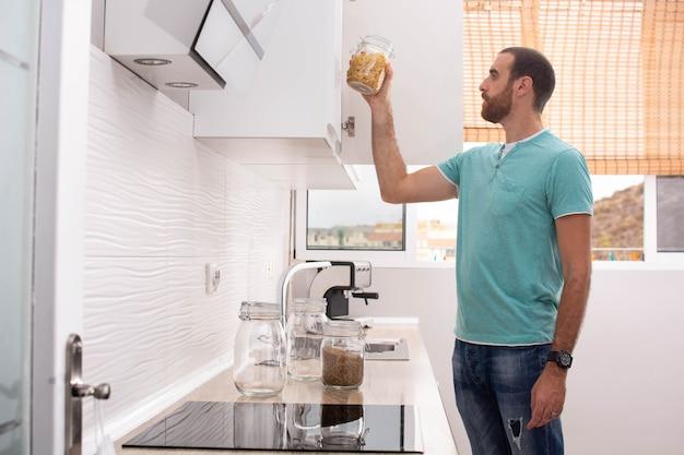 キッチンのパントリーからマカロニの鍋を拾う男