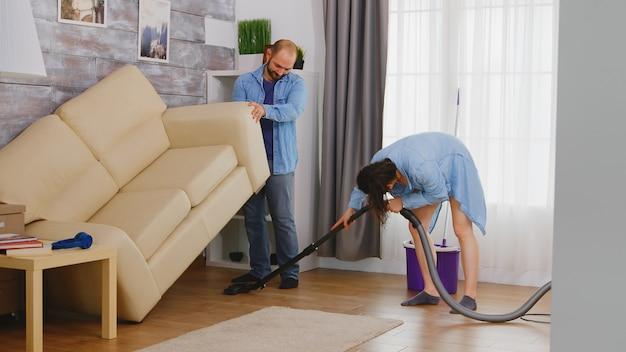 남자가 소파와 아내를 집어 들고 그 아래의 먼지를 진공 청소기로 청소합니다.