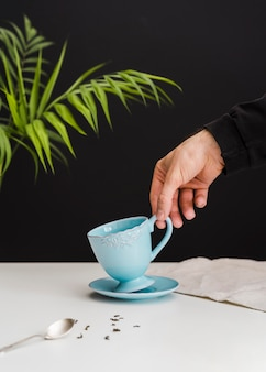 Man picking up teacup
