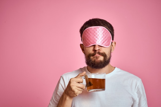 A man in a pink sleep mask with a cup of tea in his hands on an isolated background cropped view