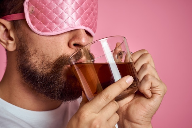 Man in a pink sleep mask with a cup of tea in his hands isolated