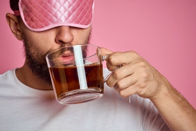 A man in a pink sleep mask with a cup of tea in his hands