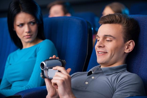 영화관에서 해적질하는 남자. 영화관에서 여자 옆에 앉아 있는 동안 홈 비디오 카메라로 촬영하는 젊은 남자