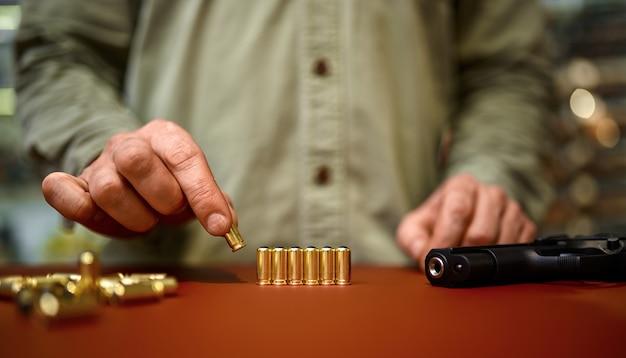 男は銃の店のカウンターに弾丸を置きます。武器屋のインテリア、弾薬と弾薬の品揃え、銃の選択、射撃の趣味とライフスタイル、護身術
