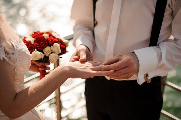 Мужчина кладет кольцо на палец своей невесты, стоящей на пирсе на берегу озера. концепция свадьбы