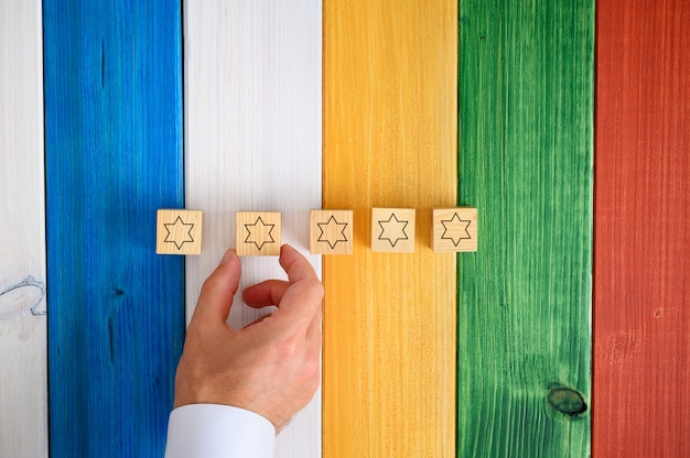 概念的なイメージでカラフルな机の上に星が付いている5つの木製の立方体を置く男。
