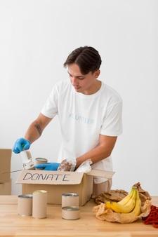 Человек кладет подарки в коробки для пожертвований