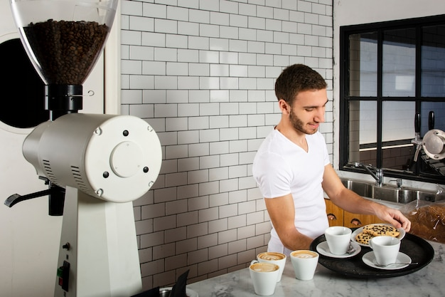 Man placing on the tray cups of coffee and cookies