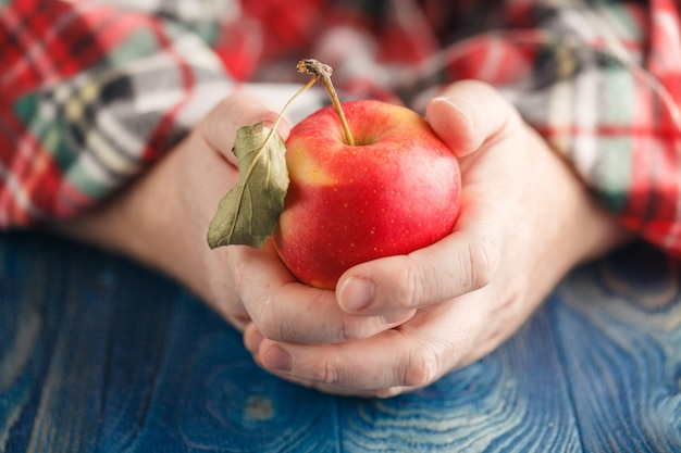 Man in plaid hold one apple