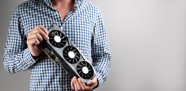 Man in plaid shirt holding grafic video card on gray background with copy space. bitcoin cloud mining.