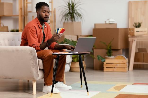 컬러 팔레트와 노트북을 사용하여 집을 재 장식하려는 남자