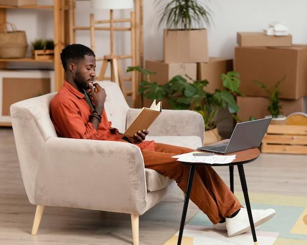 ノートパソコンと本を使用して家を改装することを計画している男