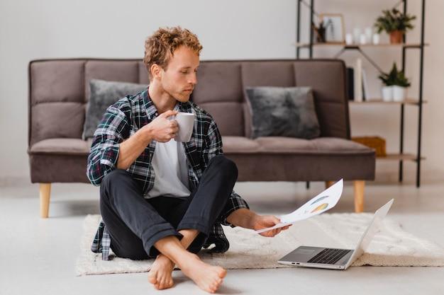 Uomo che pianifica di ridipingere la casa mentre beve il caffè